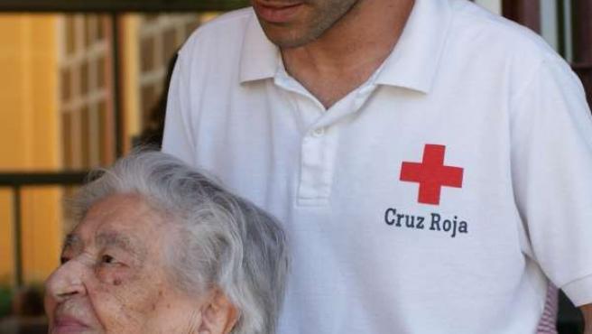 Voluntario De Cruz Roja Con Una Persona Mayor