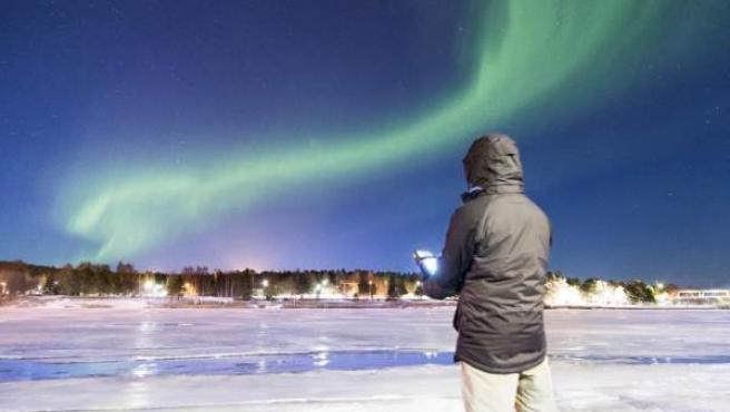 Un estudiante de la Universidad de Sevilla trabaja en su proyecto de investigación bajo la influencia de una aurora boreal en el Ártico.