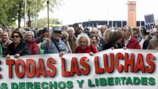 """Varios manifestantes portan una pancarta durante la protesta convocada en Madrid por las 'mareas' blanca (Sanidad), verde (Educación), naranja (Servicios Sociales) y roja (por la ciencia), con la idea de conformar una corriente """"multicolor"""" por la defensa de todos los servicios públicos."""