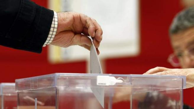 Un ciudadano ejerce su derecho al voto introduciendo el sobre con su papeleta en una de las urnas.