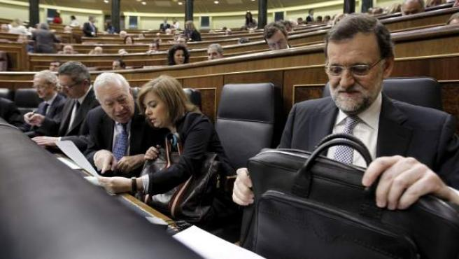El presidente del Gobierno, Mariano Rajoy (d), junto a la vicepresidenta, Soraya Sáenz de Santamaría (2d), y el ministro de Asuntos Exteriores, José Manuel García-Margallo (3d), al inicio del pleno del Congreso.