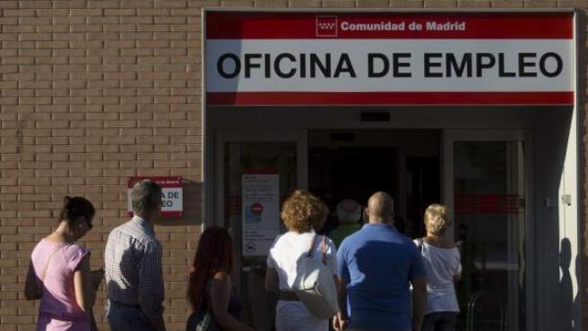 Un grupo de personas hace cola ante una oficina de empleo.
