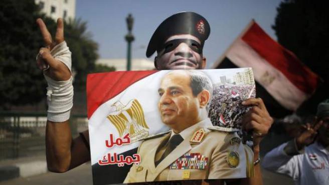 Un hombre lleva una careta y un cartel de apoyo al exministro de Defensa Abdelfatah al Sisi, candidato favorito a las elecciones presidenciales en Egipto.