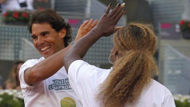 El tenista Rafa Nadal (i) choca la mano con la tenista Serena Williams, durante uno de los partidos benéficos del 'Charity Day' previo al Mutua Madrid Open de Tenis 2014.