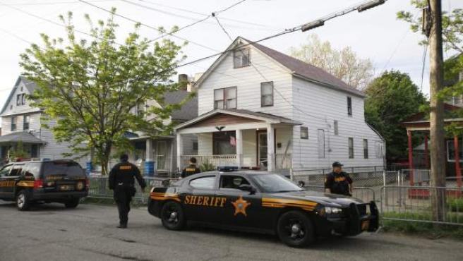 Varios agentes frente a la casa donde permanecieron secuestradas durante diez años.