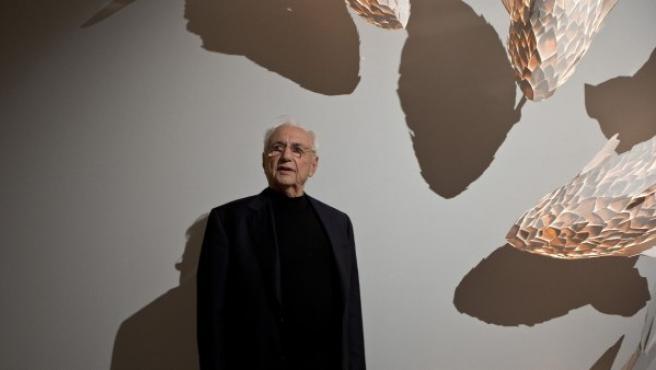 El arquitecto Frank Gehry y algunas de sus lámparas diseñadas en forma de pez.