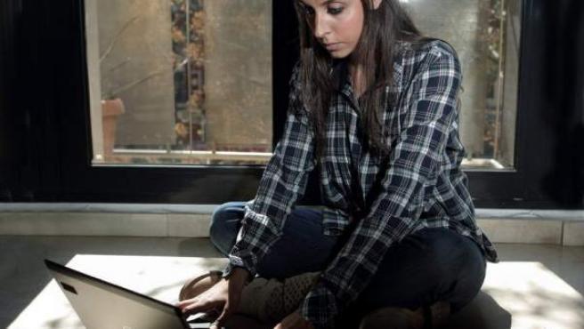 Una joven navega en Internet desde su ordenador portátil.