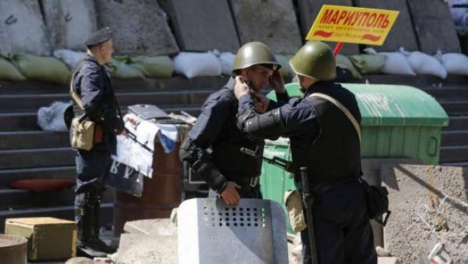 Un policía ucraniano ayuda a otro a ponerse el casco frente al Ayuntamiento de Mariupol (Ucrania).