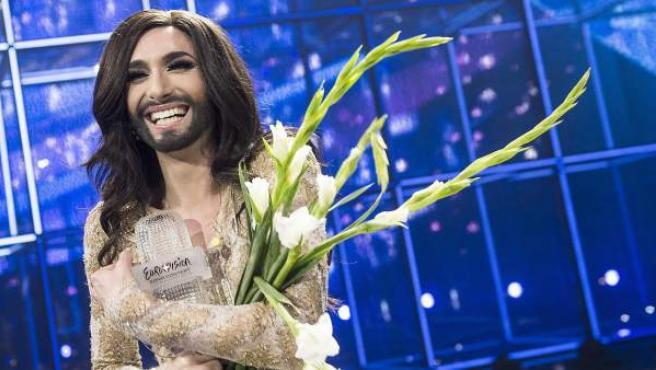 La representante austríaca, ganadora de Eurovisión 2014, sonríe mientras abraza un ramo de flores.