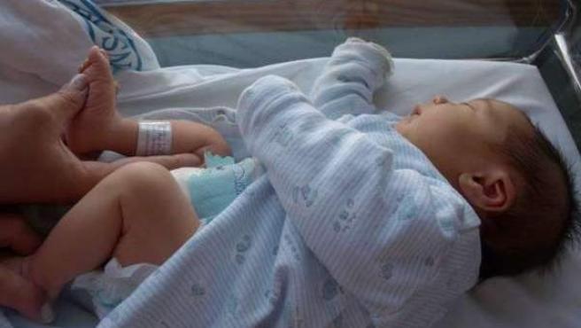 Un bebé en la cuna de un hospital.