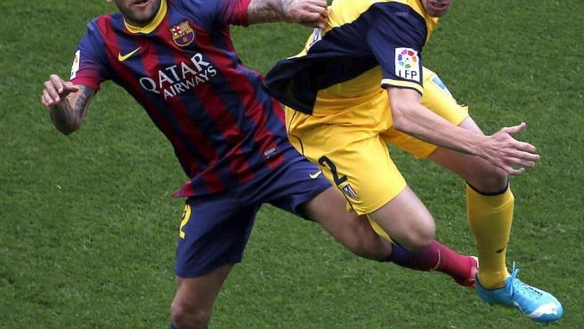 El defensa brasileño del FC Barcelona, Dani Alves (i), salta con el defensa uruguayo del Atlético de Madrid, Diego Godín (d).