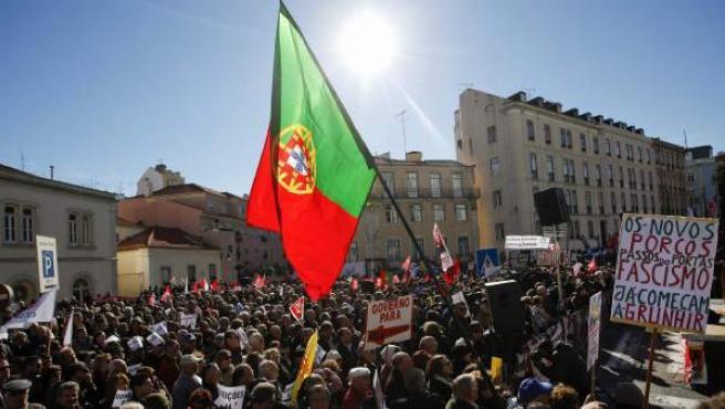 Un grupo de manifestantes con pancartas contra el Gobierno de Passos Coelho durante unas protestas en contra de los recortes aprobados en el Parlamento durante el debate sobre los Presupuestos del Estado de 2014, en Lisboa (Portugal).
