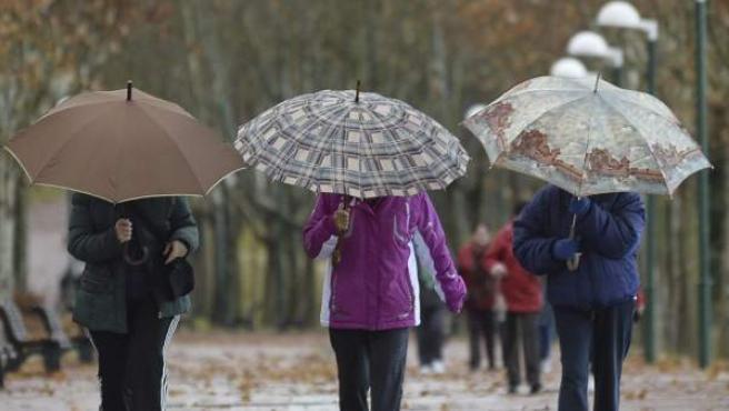 Tres mujeres caminan bajo la lluvia.