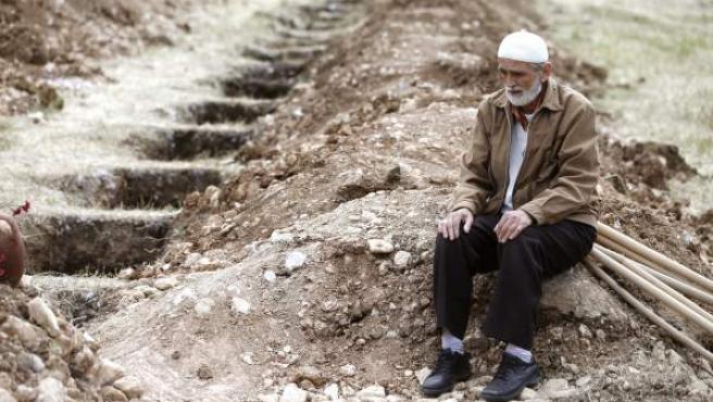 Un hombre permanece cjunto a las tumbas de los mineros que perdieron la vida en la explosión de una mina junto a Soma (Turquía).