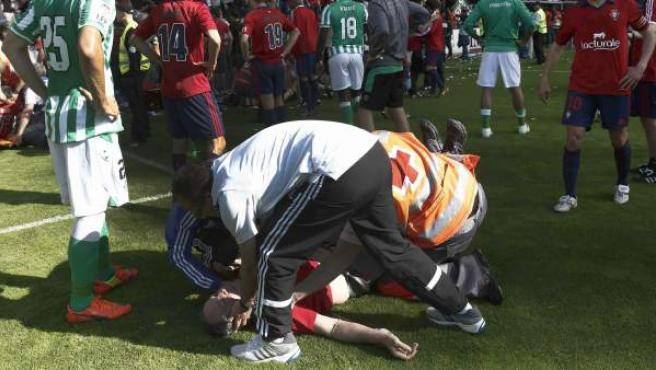 Un efectivo de Cruz Roja junto al defensa del Betis Jordi Figueras (i) socorren a uno de los heridos en la avalancha registrada en el estadio El Sadar tras el gol de Osasuna, en el minuto 12 del partido contra el Betis.