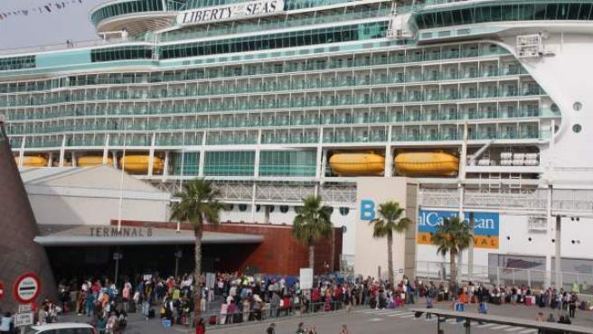 Pasajeros embarcando y desembarcando del 'Liberty of the Seas', uno de los cruceros que han atracado en el Puerto de Barcelona en una jornada de récord.