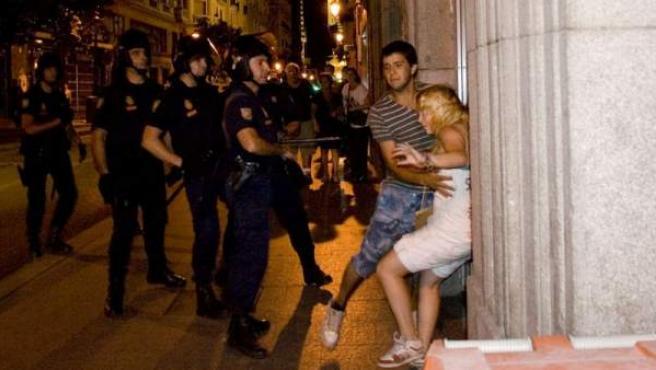 Katherina es sujetada por un amigo tras recibir un bofetón por parte del agente antidisturbios que se encuentra delante de ella.