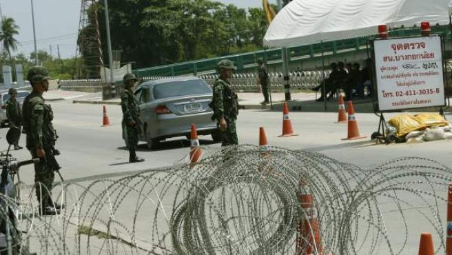 Soldados tailandeses vigilan tras una alambrada en un puesto de control montado cerca de una concentración de activistas progubernamentales en Bangkok, Tailandia.