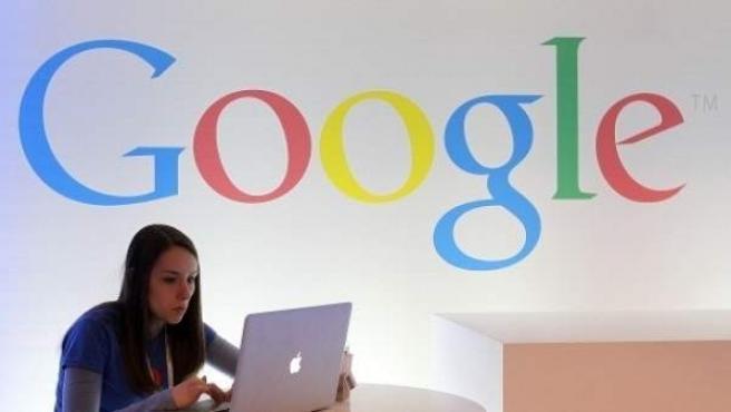 Una usuaria consulta su ordenador frente a un logo de la compañía Google.