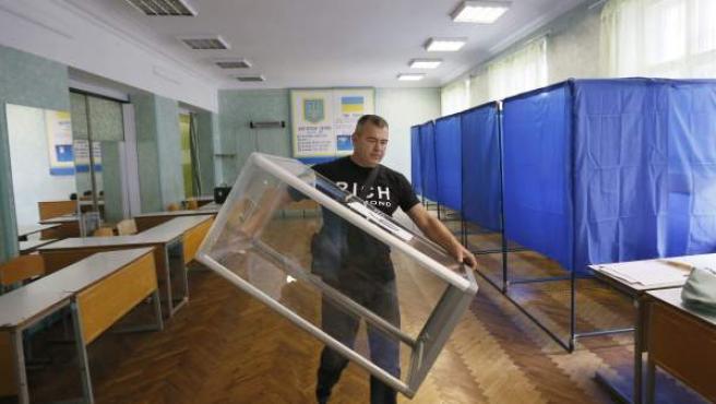 Un hombre transporta una urna de votación en un colegio electoral de Kiev (Ucrania).