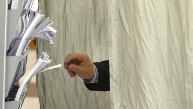 Un hombre se dispone a escoger una papeleta durante la jornada de votación de los comicios europeos en Valladolid.