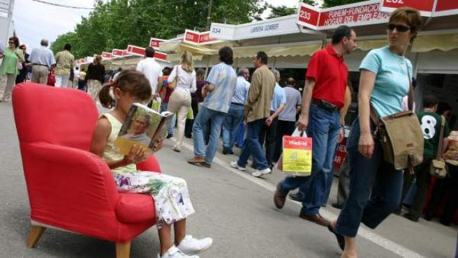 Una niña lee un libro en la Feria del Libro de Madrid.