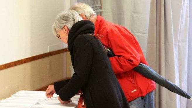 Dos personas buscan papeleta para votar en su colegio electoral en Getxo (Bizkaia).