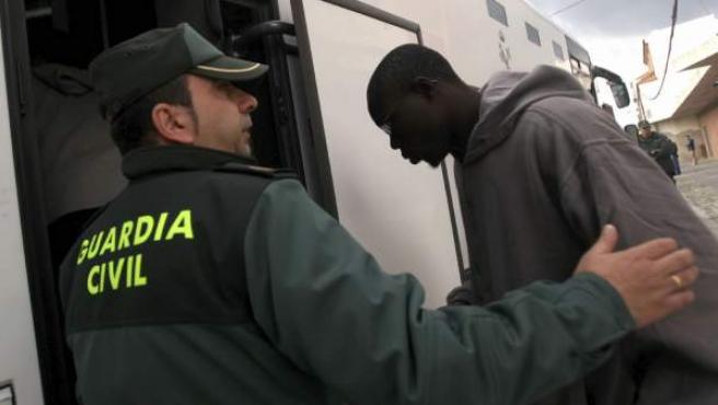 La guardia civil traslada a los once inmigrantes, de origen subsahariano, para su identificación después de que Salvamento Marítimo los rescatara.