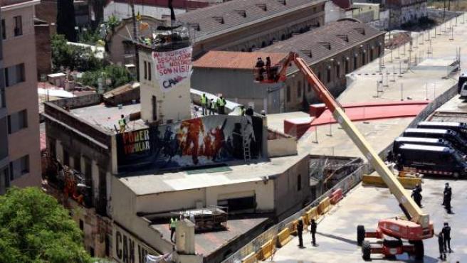 Agentes de los Mossos d'Esquadra acceden a la casa okupa Can Vies, en el barrio de Sants de Barcelona, con una grúa para desalojar a los okupas atrincherados en la torre.