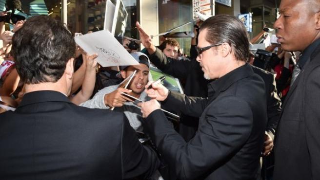 Brad Pitt firmando autógrafos en El Capitan Theatre de Hollywood, durante la premiere de 'Maléfica'.