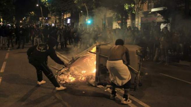 Dos jóvenes colocan un contenedor incendiado como barricada durante los incidentes tras la marcha hacia la comisaría de los Mossos d'Escuadra de Les Corts, en Barcelona.