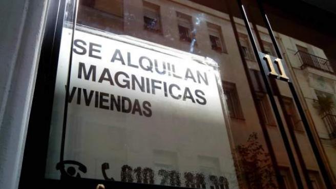 Un cartel anuncia el alquiler de viviendas en la fachada del edificio.
