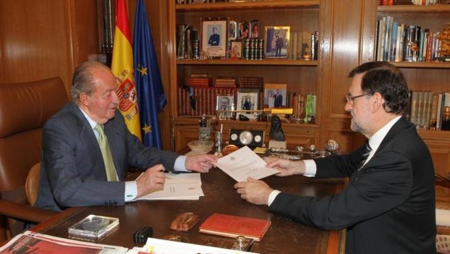 El rey entrega un documento a Mariano Rajoy en el que anuncia su abdicación al trono, en junio de 2014.
