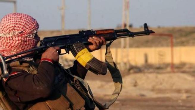 Un combatiente suní dispara su arma en un efrentamiento en la ciudad iraquí de Fallujah .