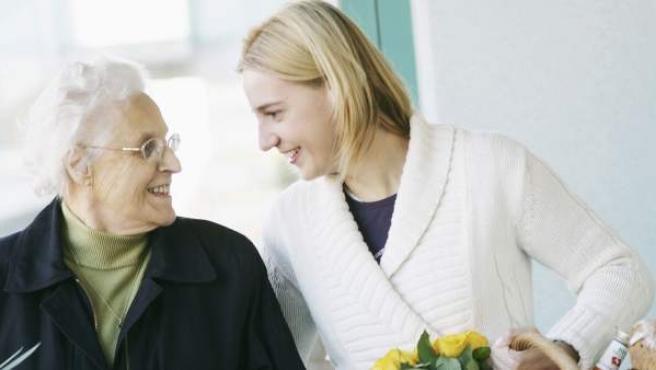 Una mujer ayuda a una señora mayor a llevarle una cesta con la compra.