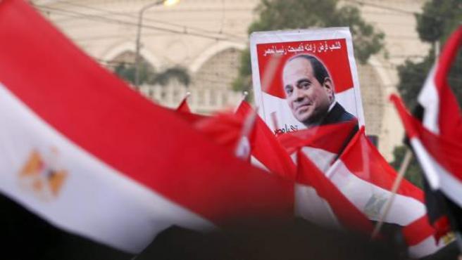 Celebración de ciudadanos egipcios al término de la ceremonia de toma de posesión del presidente electo, Abdel Fattah al-Sissi (en el cartel), junto al palacio presidencial de El Cairo, Egipto.