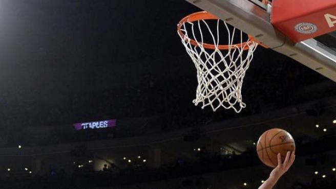 Un momento de un partido de baloncesto en el que un jugador está próximo a anotar.