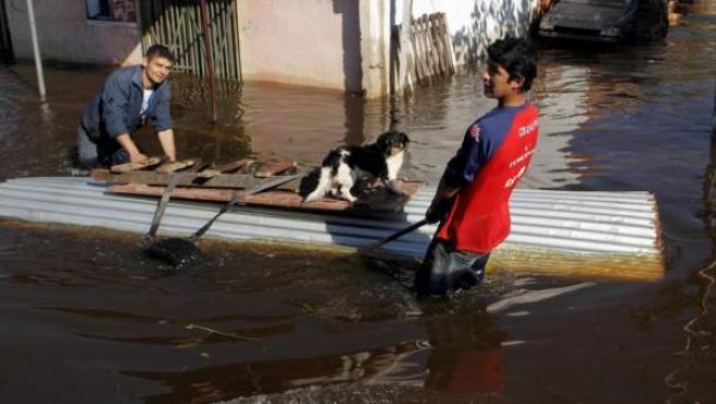 Dos hombres trasladan sus pertenencias por una calle inundada en el barrio Tacumbu de Asunción.