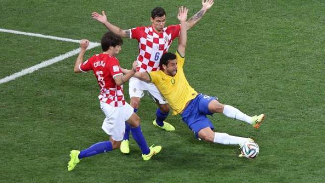 Fred se tira al suelo ante dos defensas croatas en la jugada en la que colegiado del Brasil-Croacia decretó un penalti que supondría el 2-1 en el marcador.