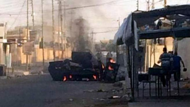 Vista de dos vehículos policiales incendiados en una calle de Tikrit, norte de Irak, este miércoles 11 de junio de 2014.