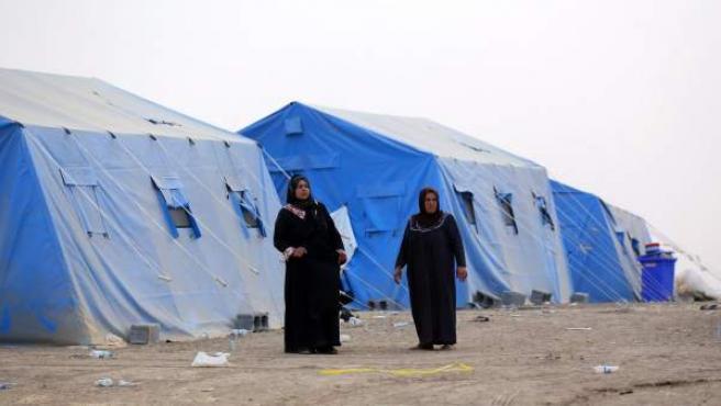 Mujeres refugiadas iraquíes caminan frente a las tiendas para el almacenamiento de ayuda humanitaria.