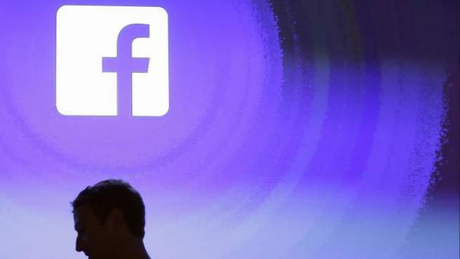 Mark Zuckerberg pasa por delante del logotipo de Facebook.