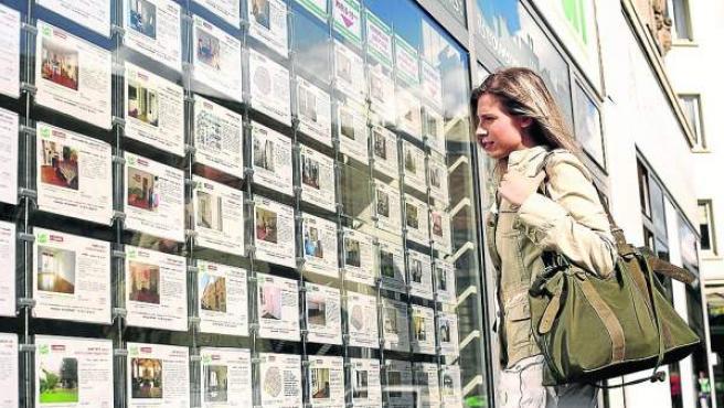 Una chica contempla los anuncios de viviendas en una inmobilaria.