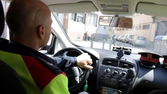 Dos agentes de los Mossos d'Esquadra patrullan en su coche logotipado.