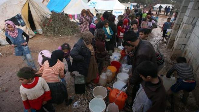 Unos refugiados hacen cola para coger agua en el campamento de refugiados de Atmeh, en la provincia norteña de Idlib, en Siria.