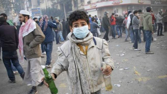 Un menor sostiene un cóctel molotov durante unos disturbios con la policía en Egipto.
