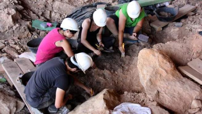 Tres arqueólogos trabajan en los restos de una gran hoguera que los neandertales podían usar para hacer fuegos rituales.