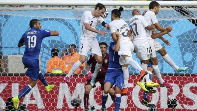 El defensa uruguayo Diego Godín (2i) remata de cabeza para marcar el único gol del partido Italia-Uruguay, del Grupo D del Mundial de Fútbol de Brasil 2014.