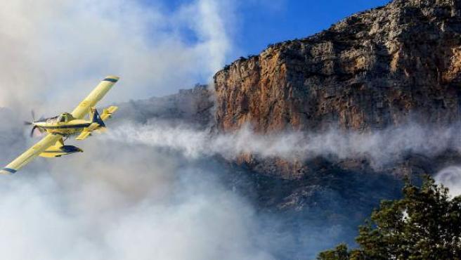 Una avioneta vierte agua durante las labores de extinción del incendio forestal declarado a los pies del Parque Natural del Montgó, en el término municipal de Dénia (Alicante).