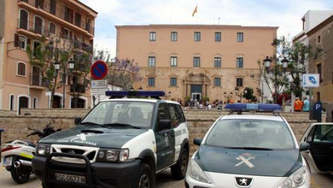 Vehículos de la Guardia Civil ante el Ayuntamiento de Torredembarra, que ha sido registrado en busca de pruebas sobre adjudicaciones irregulares mientras algunos curiosos se acercaban al edificio.